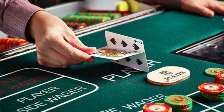 kuva baccarat pelipöydästä kasinolla jossa jakajalla kortit edessä