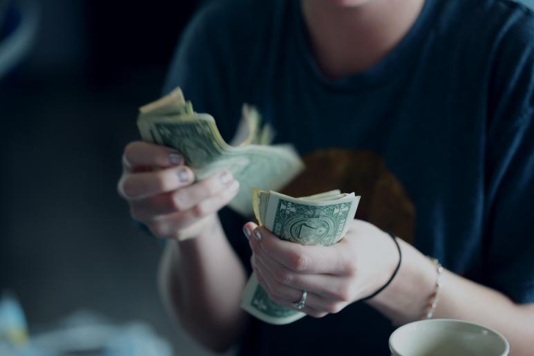 naisella on nippu seteleitä kädessä