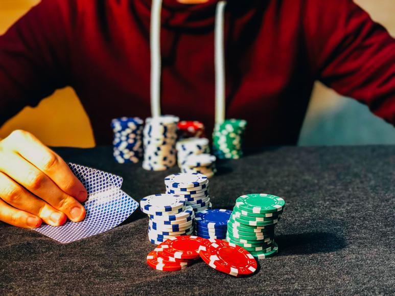 mies pelaa panoksilla uhkapeliä ja pitää kortteja kädessään